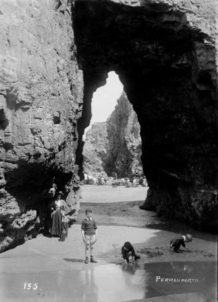 Children playing in a pool at the foot of Arch Rock