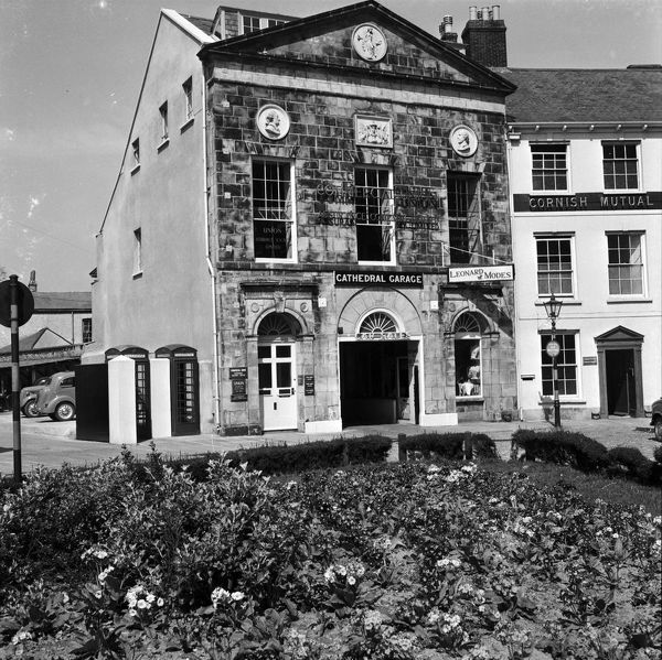 Looking across the flower beds to Cathedral Garage and car park. Signage for the Commercial Union Assurance company can be seen on the upper part of the building. The Cornish Mutual Assurance company occupied the building next door. Photographer