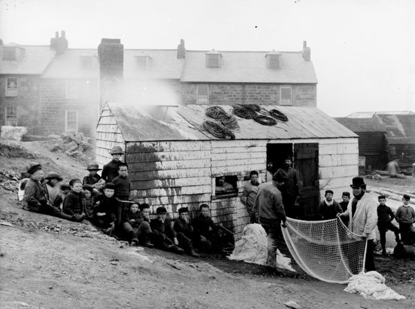 The Bark House, used for treating rope and nets, backing on to Burrow Road, with fishermen and a group of boys. Photographer: Edward Ashton
