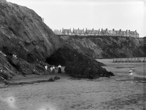 A group of women and children on the beach. On the right hand side a line of wheeled beach huts can be seen and on the cliff top a line of buildings. Photographer: Samuel John Govier
