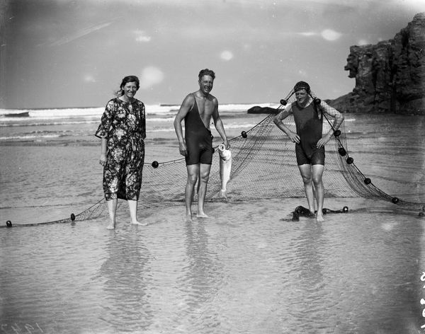 A woman and 2 men in swimsuits on Perranporth beach, one man is holding a fish whilst the other has the net over his head. Photographer: Arthur William Jordan