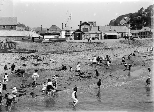 The beach crowded with children paddling, playing and exploring, with a view of East Looe in the background including the lifeboat station. Photographer: Herbert Hughes