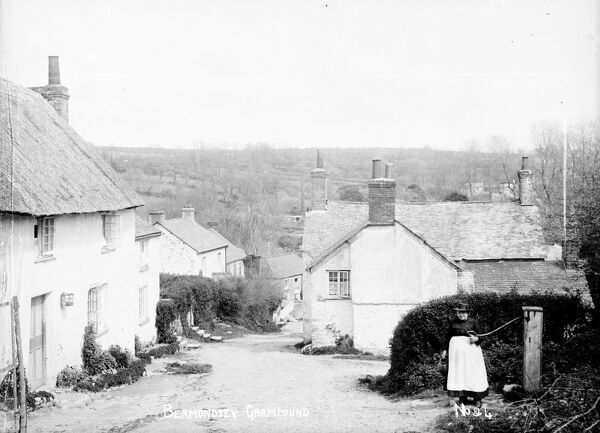 A view down Old Hill from the water pump on the right. A lady is pumping water. Photographer: Samuel John Govier