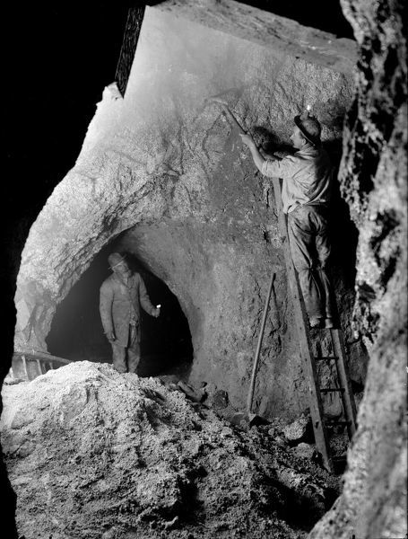 Miner undertaking overhand stoping. The working miner is shown on a ladder while stoping with a candle affixed to his helmet. A supervisor is shown below holding a candle. The mine was then worked with Penhalls. Photographer: John Charles Burrow