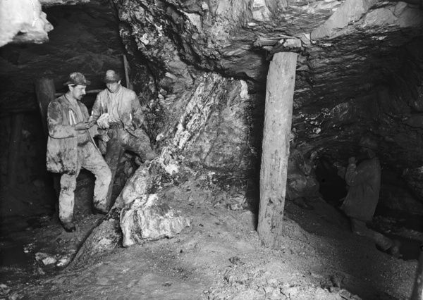 Group of miners working underground (60 fathom level) looking west at Blue Hills mine, St Agnes, Cornwall, showing the heave (or crosscourse). The faulting vein behind the prop consists almost entirely of white quartz, containing crystals of iron pyrites