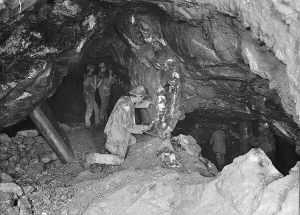 Showing the heave (or crosscourse) looking east, 66 fathom level. Two miners are shown boring at the point where the lode is cut off. Photographed by J.C. Burrow