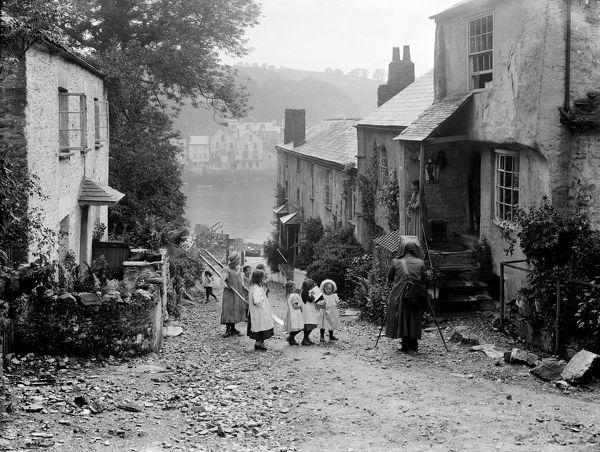 A view from a street in Bodinnick looking down towards the river and Fowey opposite. Children observe a photographer. Photographer: H. Hughes