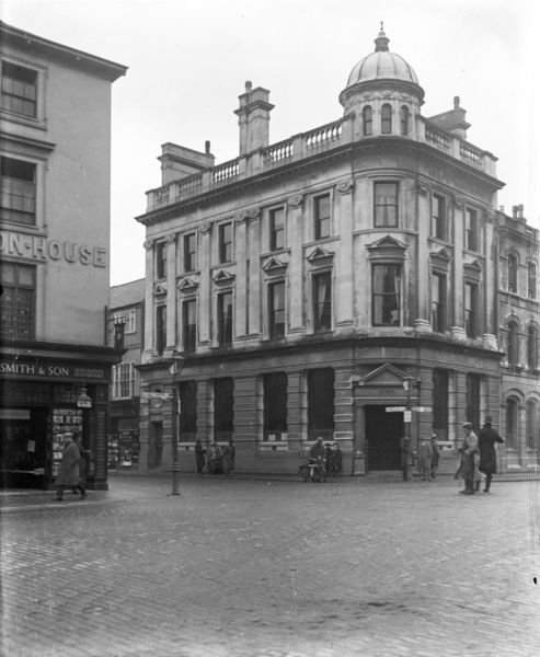 Lloyds Bank on the corner of Boscawen Street and Lower Lemon Street, taken from Boscawen Street. There are several people and a motorbike in the photograph. Photographer: Arthur William Jordan