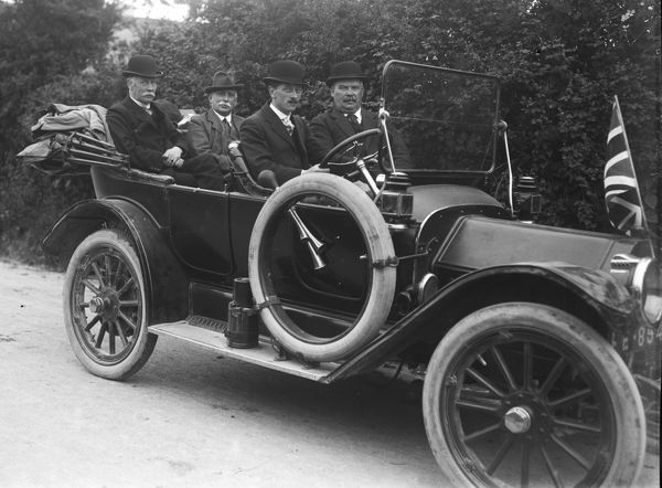 A Buick motor car carrying four male passengers. The number plate is only partially visible. There is a union jack flying on the bonnet of the car. Photographer: Unknown