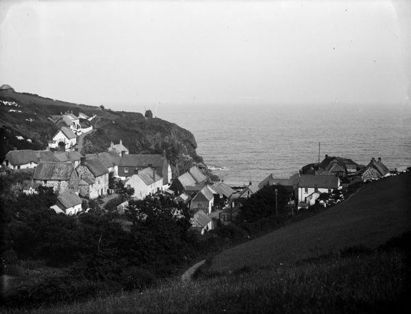 The village and cove, viewed from inland, with the coastguard's residence visible on the cliffs. Photographer: Herbert Hughes