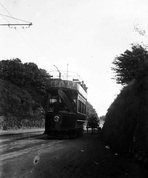 Open top tram number 4 approaching the west end of Redruth, alongside a horse and carriage. It is advertising the company 'Moffatt' of Camborne. The tramway opened for passengers on 7th November 1902 and ran until the 29th September 1927