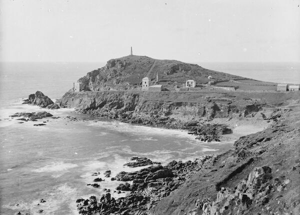 A good view of Cape Cornwall with two disused mine stacks, two engine houses, dwelling houses and a group of people near what appears to be a swing in the garden of a house, there are a number of boats on the beach