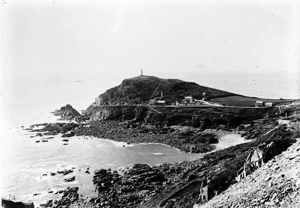 A general view of Cape Cornwall with two stacks and engine houses. Smoke rises from a chimney in the building adjacent to the engine house. A large dwelling house with garden centre ground, a barn and cottage stand along the road to the right of the picture