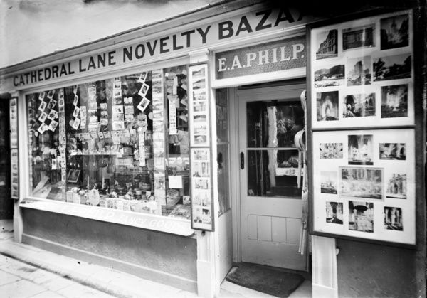 View of E.A. Philp's shop the 'Cathedral Lane Novelty Bazaar' at No. 9, Cathedral Lane, Truro. The shop front displays photographs of Truro Cathedral and elsewhere. Photographer: Possibly Arthur William Jordan or Arthur Philp