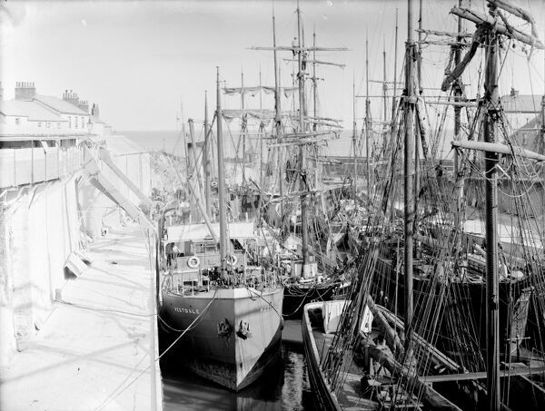 Charlestown harbour looking out to sea. The harbour is full of a mixture of both steam and sail shipping. SS Westdale on the east quay, (left of picture) is steel built and screw driven. She was built in South Shields in 1911 and owned in Liverpool
