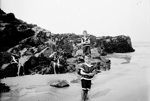Three boys and a girl dressed in beach clothes playing at St. George's Cove. Early 1900s. Photographer: T.H. William's
