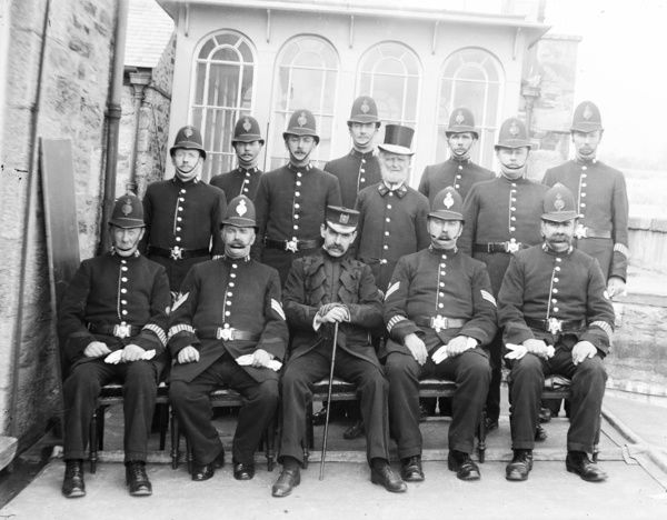 A group of Truro police under Superintendent Angel, with the town crier, John Odgers, wearing a top hat, on the roof of the City Hall, Boscawen Street. Photographer: Unknown