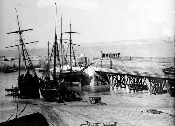 Three sailing coasters unloading at the central jetty and harbour beach. 'Hetty' on the right and 'Vixen' in the centre. 'Vixen' was built at Peterhead in 1870 and registered in Fowey