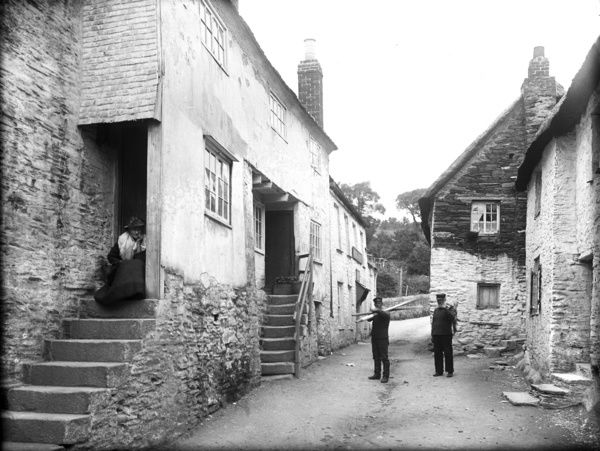 A street view of a row of cottages with steps to high entrance doors. An elderly woman sits at the top of the steps in the foreground. Two fisherman stand in the street, one with oars over his shoulder. The 'Rising Sun' inn is just behind them