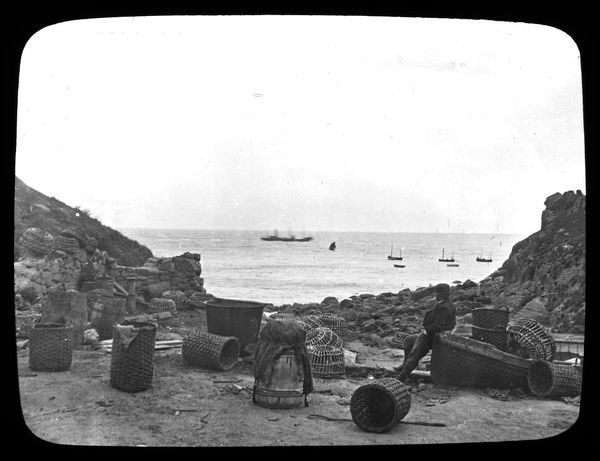 A view of a man leaning on a boat, surrounded by crab and lobster pots, looking out at the fishing boats in the bay at low tide. Photographer: Possibly W.T