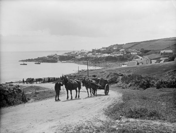 A horse and cart comes up the road from the village. Photographer: Herbert Hughes
