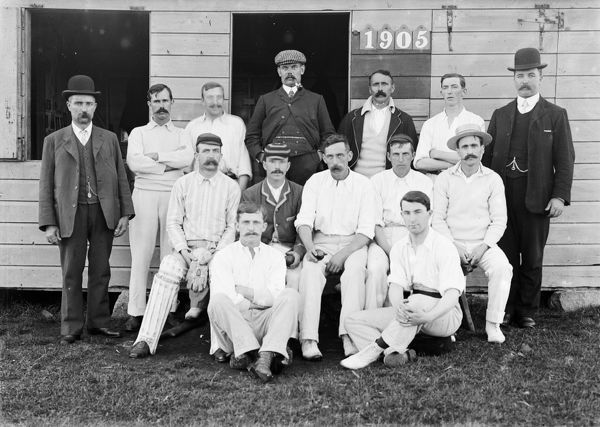 Unidentified cricket team posing outside a club house. Photograph possibly taken at Truro Cricket Club. Photographer: Unknown