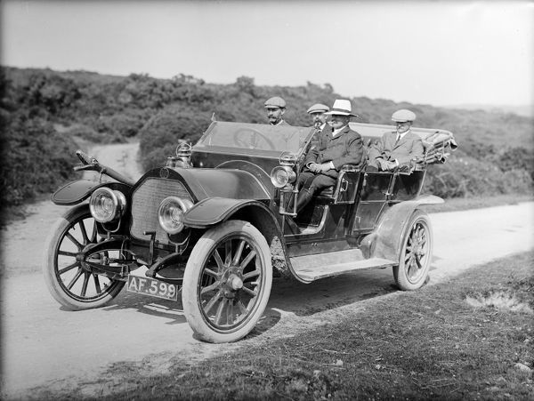 "Photograph entitled ""The Motor on the Roadside"" of a Darracq 25/30, registered in Oct 1910 to J.T. Taylors Garage, Penzance: registration number AF 599. Herbert Hughes is driving and J.C. Burrow is sitting in the back on the right"