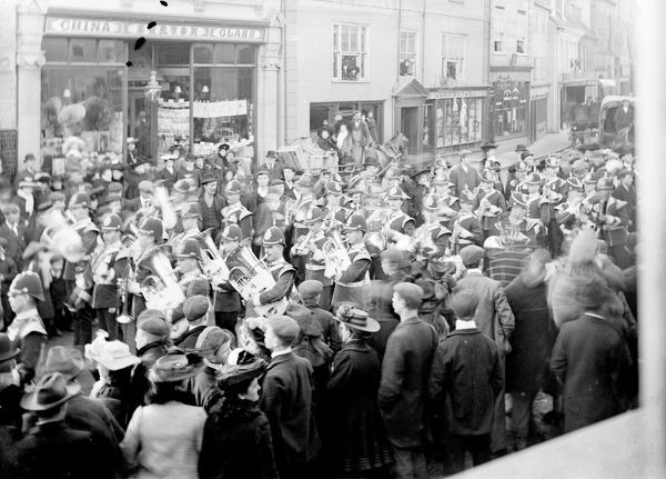 Duke of Cornwall's Light Infantry military brass band processing through the street, closely watched by onlookers on either side. Photographer: A.W. Jordan