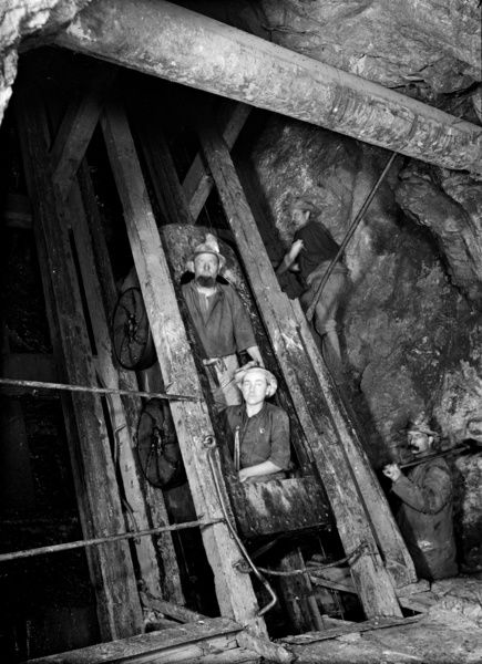 Two miners being raised to the surface in a Single Decker gig on skip road at 302 fathoms in Eastern Shaft. Photographer: John Charles Burrow