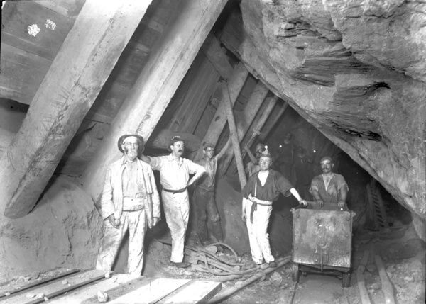 Miners at the 440 fathom level, Dolcoath mine, in March 1903. Includes mining tram on tracks. Photographed by J.C. Burrow in 1893