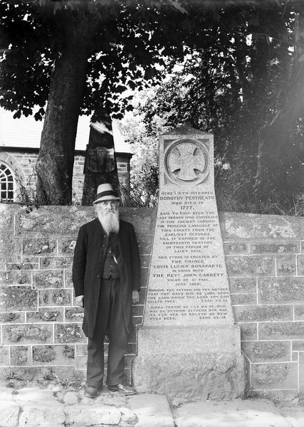 A view of Dolly Pentreath's memorial set in the wall of Paul churchyard with an elderly bearded gentleman standing by the side