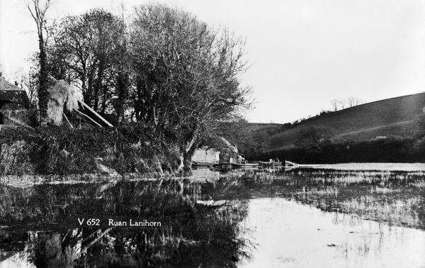The estuary below the village of Ruan Lanihorne with a very high tide. A boat with two people can be seen. Photographer: Arthur William Jordan