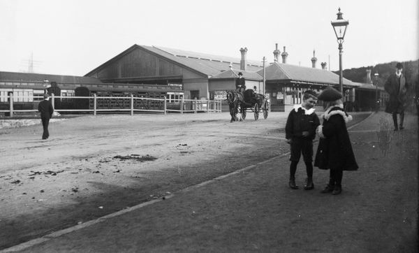 Exterior view of Falmouth Railway Station, with children in the foreground