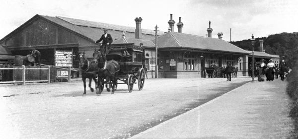 Exterior view of Falmouth Railway Station, with horse drawn carriages