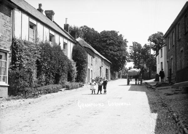 View up Fore Street, Grampound, near the top of the village. Children and a horse and cart are posed in the street. Photographer: Samuel John Govier