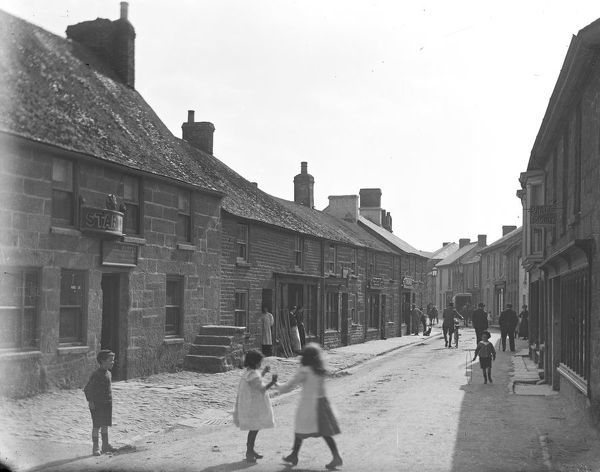 Fore Street, Churchtown, with children in the foreground and the Star Inn on the left. Samuel Warren was the innkeeper in 1910 but by 1914 it was William Stephens. The photograph also shows several shops including Rowe's, Ironmonger and Grocer and a Fruiterer