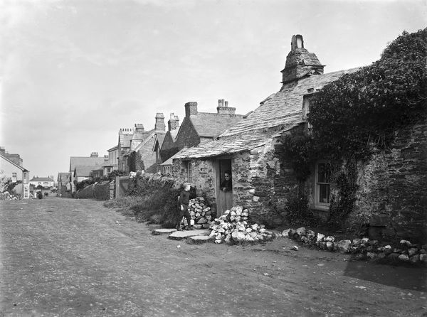 A view along Trevena's main street looking north west. A young boy stands talking to a lady in a doorway. Photographer: John Charles Burrow