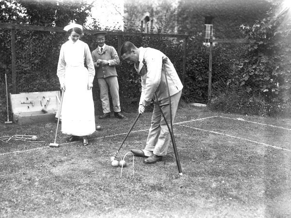 A patient, leaning on a crutch, and a smiling nurse, playing croquet, to the enjoyment of an onlooker. Photographer: Arthur William Jordan