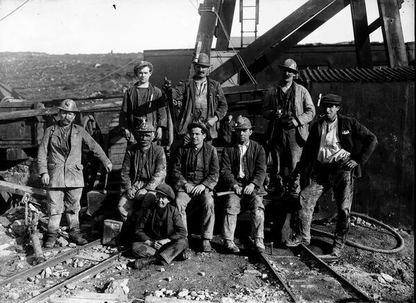 Miners posed at surface of Wheel Carne shaft, holding timber working tools including an axe, saw and lump hammer. Two workers have carbide lamps, the rest have candles. The worker on the right smoking a pipe is wearing the jacket from a military uniform