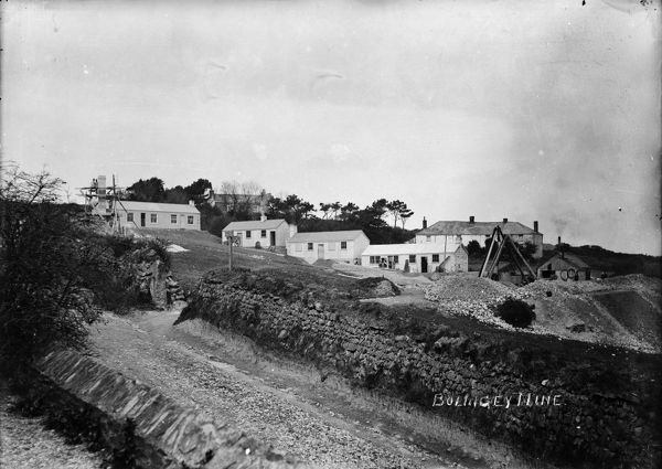 General surface view of Alfred mine, Perranzabuloe, Cornwall,showing buildings, shed and miners. On the left, miners are building a chimney stack with scaffolding and ladder. On the right a triangle of timbers with winding gear and a pulley over a shaft