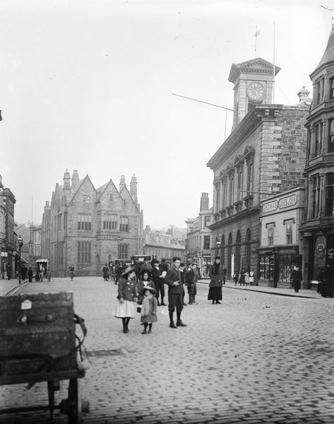 A general view of Boscawen Street looking east with children in the centre. Horse drawn vehicles can be seen outside the Coinage Hall. City Hall, with it's black-faced clock, can be seen on the right together with store front of Thomas James John
