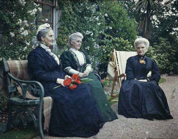A group of three women from the Gill family seated on a deckchair and a bench in the garden of Comprigney House