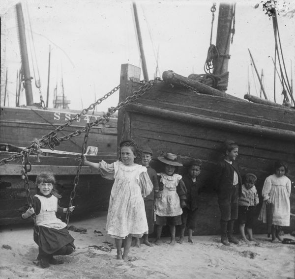 A group of young children consisting of four girls and four boys posed by two fishing vessels with the inner lighthouse on Smeaton's pier in the background. Photographer: Unknown