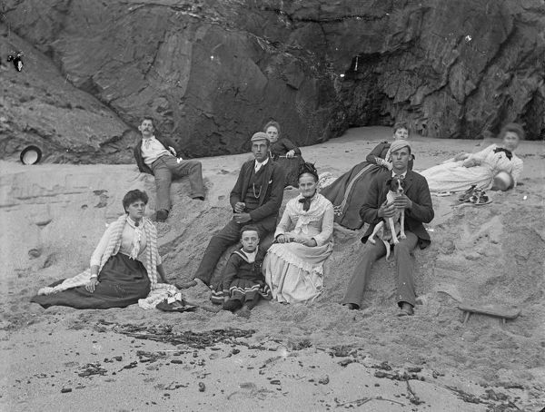 A group of men and women with a child and a dog on the beach. Photographer: Thomas Henry Williams