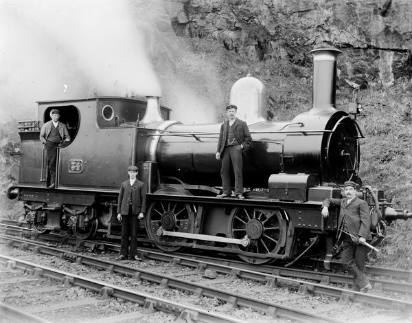 The image shows GWR number 34 pictured with two unnamed men, Charlie Gould the fireman standing on the running plate and the driver Nickie Curnow standing with his feeder (oil can) on the St Ives branch line. The engine itself has a 0-4-4 tank