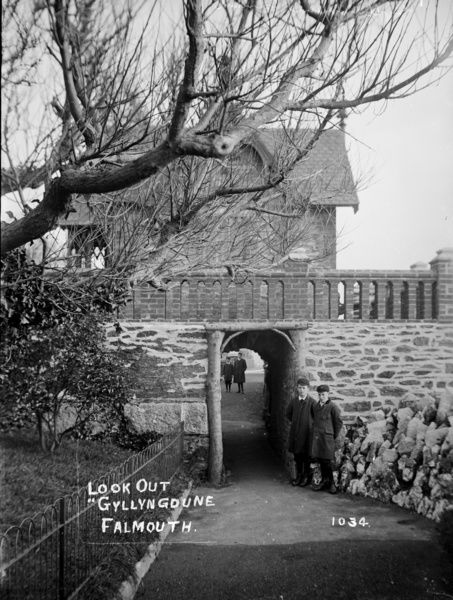 The Look-Out at Gyllngdune. Street leading through narrow tunnel under bridge, showing Look-Out building on bridge above. Two schoolboys posing for camera at tunnel entrance. Early 1900s. Photographer : Philp