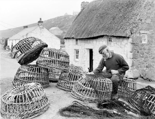 """Is it worth mending?"" Bill Harvey inspecting fishing nets surrounded by lobster pots in front of a thatched cottage at Porthgwarra. He was aged 58 when the photograph was taken. Bill is dressed in rubber boots and corduroy trousers"