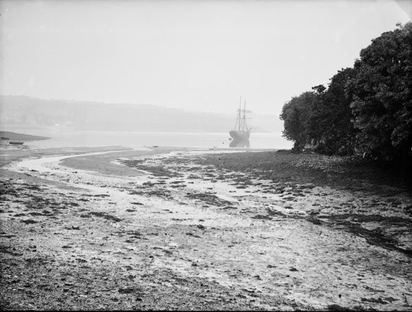The entrance to Helford creek at low tide. A topsail schooner can be seen off the estuary and Helford Passage in the distance. Photographer: Herbert Hughes