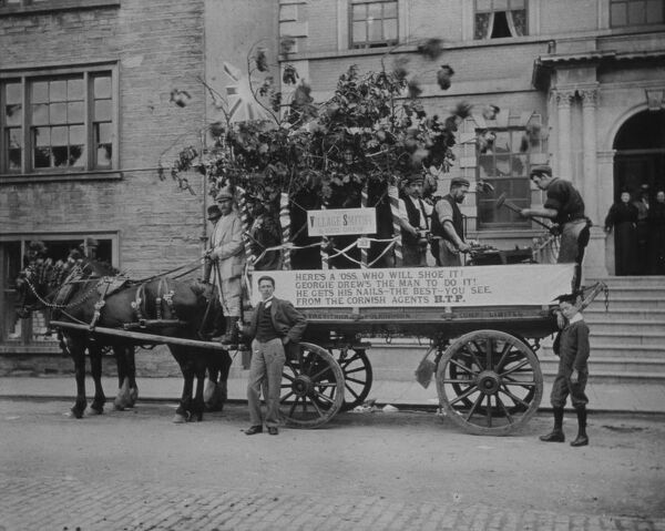 "Horse drawn float decorated to celebrate Queen Victoria's diamond jubilee. ""Here's a oss, who will shoe it? Georgie Drew's the man to do it! He gets his nails - the best - you see, from the Cornish agents H.T.P."". Photographer: Argall"