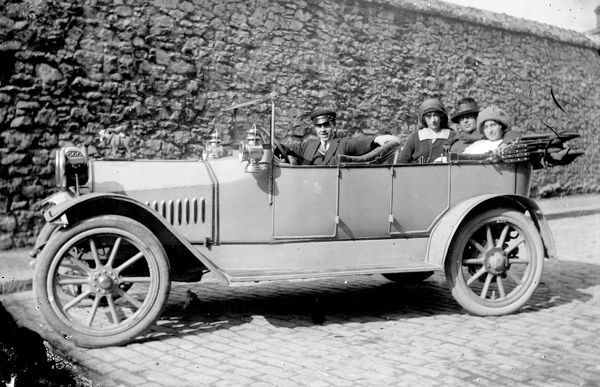 A Hupmobile Tourer motor car, with a horse mascot on the bonnet. There are three passengers and the driver wears a cap so is possibly a chauffeur. Photographer: T.H. Williams